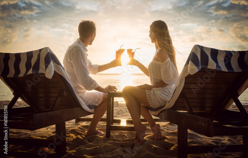 Paar mit Cocktails am Strand auf Strandliegen schaut den Sonnenuntergang im Urlaub an