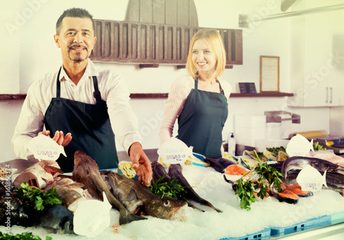 Positive cheerful shop assistants selling fresh fish Poster