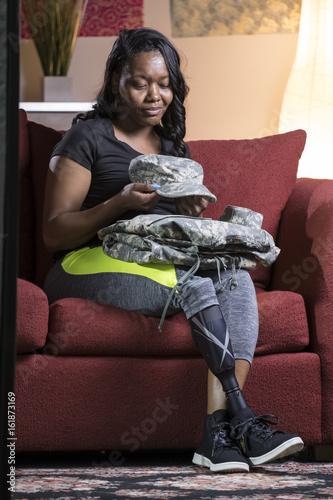 Black female veteran amputee looking at her fatigues Poster