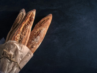 Three freshly baked baguettes on the table.