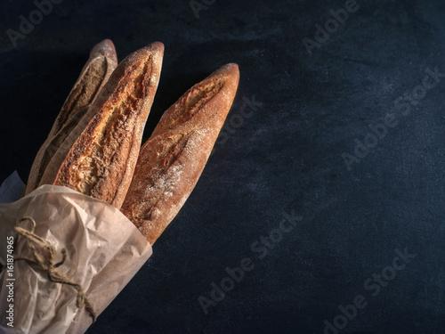 Fototapeta Three freshly baked baguettes on the table.
