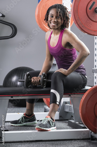 Portrait of a black woman with a barbell at the gym