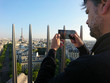 Man taking a picture of Paris in a sunny day with Eiffel Tower