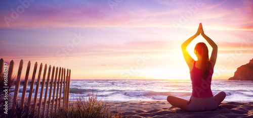 Wall mural Woman Doing Yoga Fitness In The Beach At Sunset