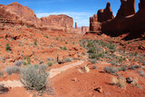 Amazing Utah landscape with red sandstones in Arches National Park, Moab, Utah, USA. Nature red sandstone sculptures with sparse green bushes on a foreground against bright blue sky.Nature background.