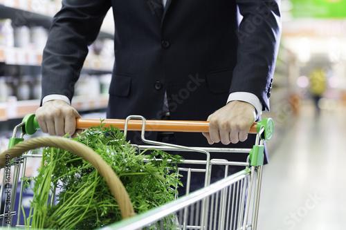 Mann fährt einen Einkaufswagen durch den Lebensmittelmarkt