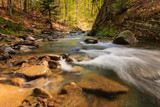 Fototapety View of mountain river with small waterfall and rapids at sunny day. Big mossy stones and boulders on river bank. Fast jet of water at slow shutter speeds give a beautiful magic effect.
