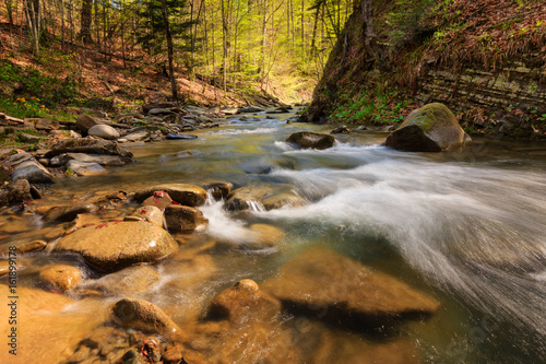 View of mountain river with small waterfall and rapids at sunny day. Big mossy stones and boulders on river bank. Fast jet of water at slow shutter speeds give a beautiful magic effect.
