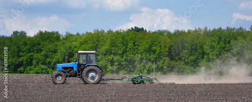 A blue tractor plows the field in the spring