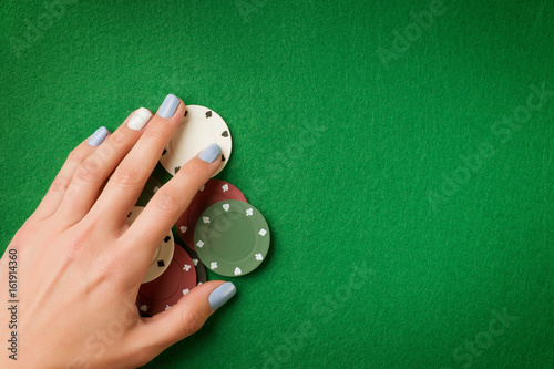 Woman hand holding poker chips on green casino felt background Poster