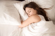 Leinwanddruck Bild - Top view of attractive young woman sleeping well in bed hugging soft white pillow. Teenage girl resting, good night sleep concept. Lady enjoys fresh soft bedding linen and mattress in bedroom
