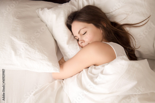 Leinwanddruck Bild Top view of attractive young woman sleeping well in bed hugging soft white pillow. Teenage girl resting, good night sleep concept. Lady enjoys fresh soft bedding linen and mattress in bedroom