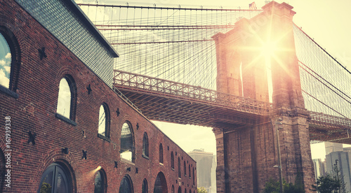Deurstickers New York Brooklyn Bridge at sunset with lens flare, color toning applied, New York City, USA.