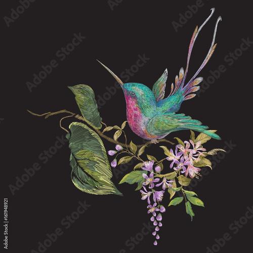 Haft moda wzór z kolibry na gałęzi egzotycznych kwiatów.