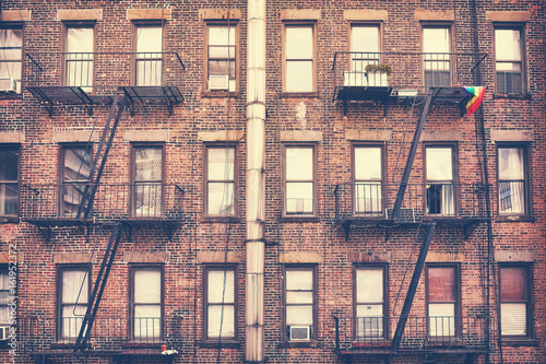 Old film retro style photo of a building with fire escape, one of New York City symbols, USA. - 161952372