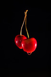 Wet red cherries on the black isolated background