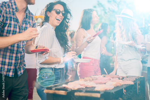 Group of friends eating, drinking, dancing and having a good time at outdoor party - 161970173