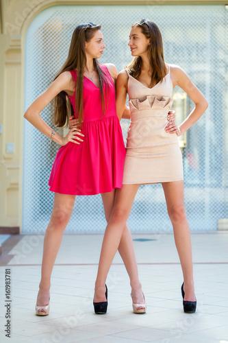 Two beautiful women in summer dresses. Studio portrait