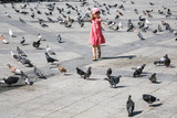 girl chasing pigeons on urban square in Athens