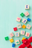 Wooden cubes with numbers and colorful toy bricks on a turquoise wooden background. - 161990737