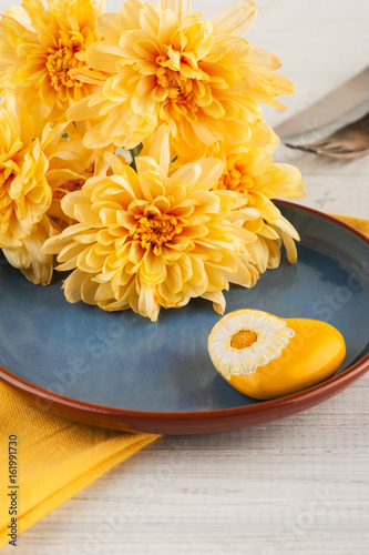 Chrisanthemum flowers on a plate on a wooden table