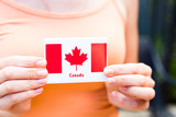 Young caucasian girl holding Canadian flag