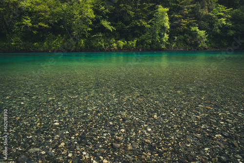 Turquoise river in a forest.
