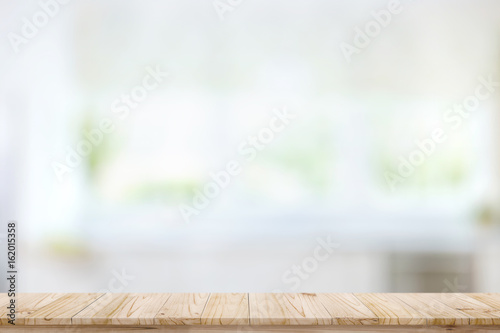 Empty wood table top on blur kitchen window background. For product or foods montage.