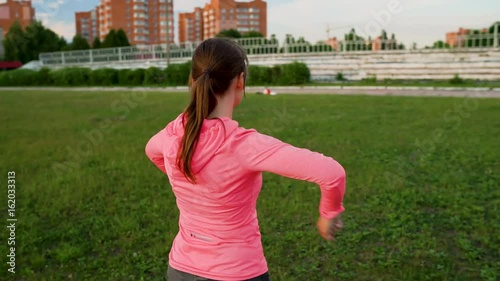 Fitness woman warms up and stretching at the stadium before run