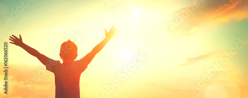 Fotobehang Zwavel geel Little boy raising hands over sunset sky, enjoying life and nature