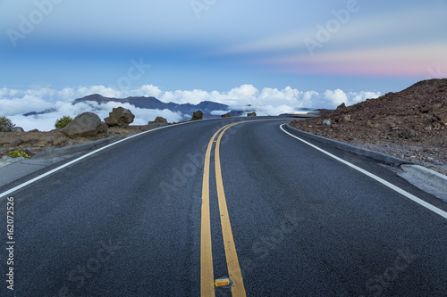 Mountain road above the clouds after sunset