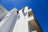 industrial alpinist work on white wall - 162073930