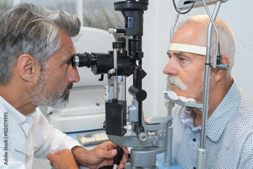 Juliste old man having her eyes examined by eye doctor