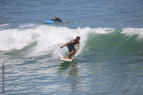 Surfing Man Leans, in Shorts on LongBoard, SUNNY View2.0