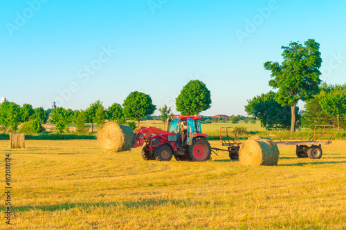 The tractor collects hay on the field