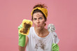 Portrait of aggravated woman with dirty face wearing yellow headband and white T-shirt holding bast whisp and abstergent posing over pink wall. Tired irritated untidy woman doing domestic work