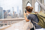 Tourist on Brooklyn bridge taking picture of scenery - 162108598