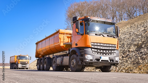 Fototapeta Zwei orange LKW`s liefern Baumaterialien für eine neue Straßendecke