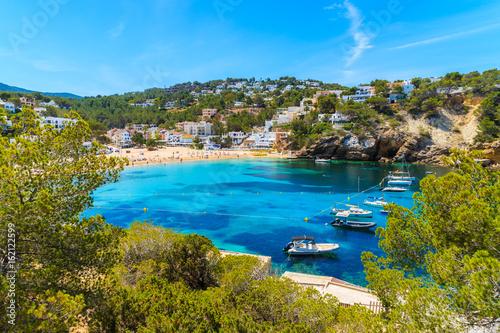 Foto op Plexiglas Cyprus Fishing and sailing boats on blue sea water in Cala Vadella bay, Ibiza island, Spain