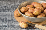 Potatoes. Young early potatoes in an old metal bowl on a wooden background. - 162132580