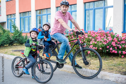 Family cycling, father with happy kid riding bike outdoors