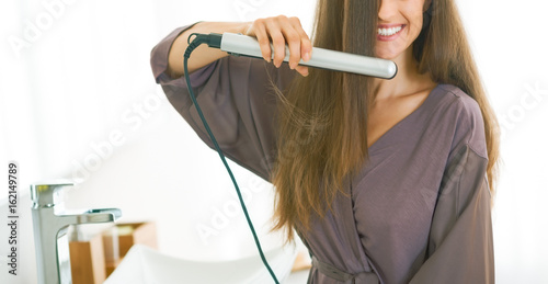 Happy young woman straightening hair in bathroom Poster
