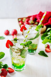 Alcoholic and non-alcoholic refreshing drinks, cold sparkling cocktail with ice, green mint and fresh strawberries in a beautiful glass on a light background