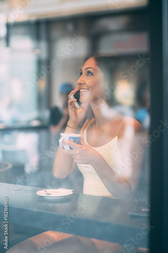 Young woman talking on phone in coffee shop Poster