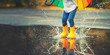 Leinwanddruck Bild - Feet of  child in yellow rubber boots jumping over  puddle in rain