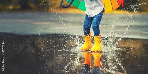 Leinwanddruck Bild Feet of  child in yellow rubber boots jumping over  puddle in rain