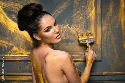 Sexy brunnette woman paints room to gold