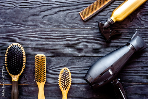 Brushes, hairdryer and hairspray on grey wooden background top view space for text