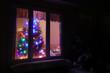 Glowing Christmas tree in the window. Snowy winter night scene. Winter holidays background, Christmas background, New Year background. Good for greeting card.