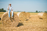 Smiling farmer sitting on an hay bale in his field - 162182732